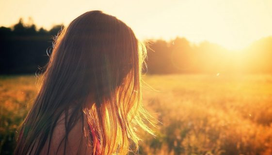 young woman standing in meadow looking at trees at sunset